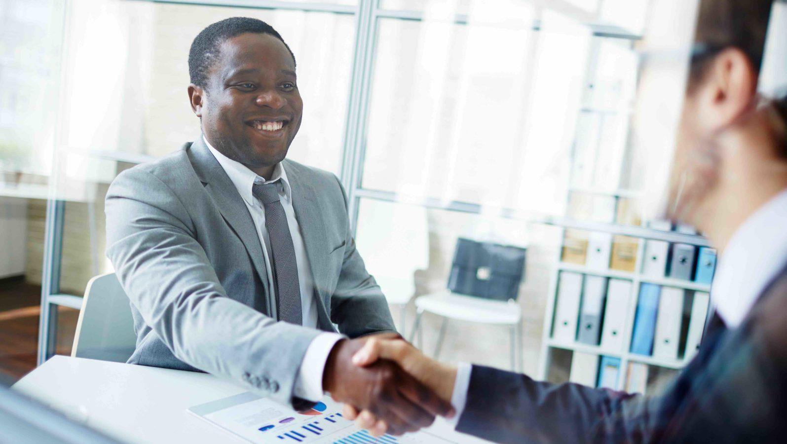 job interview, shaking hands at desk